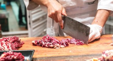 chef-cutting-fresh-raw-meat-wooden-board_1112-2469